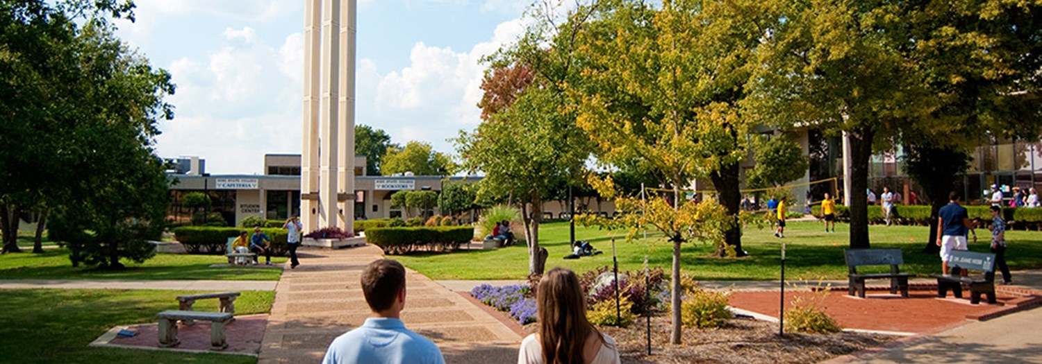 View of the central campus mall, two students, and the logo tower.
