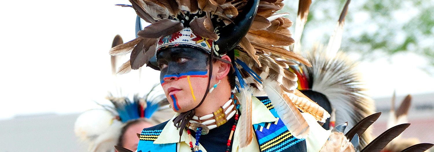 Young Native American male in full costume and face paint