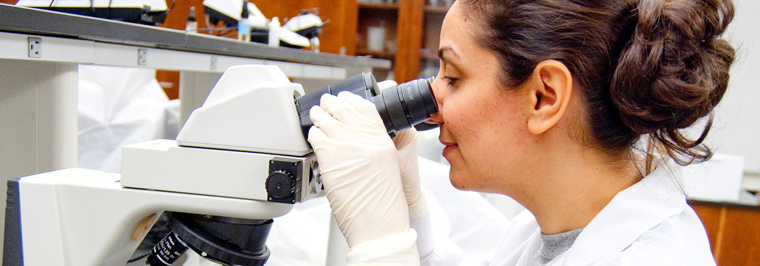 lady looking through a microscope