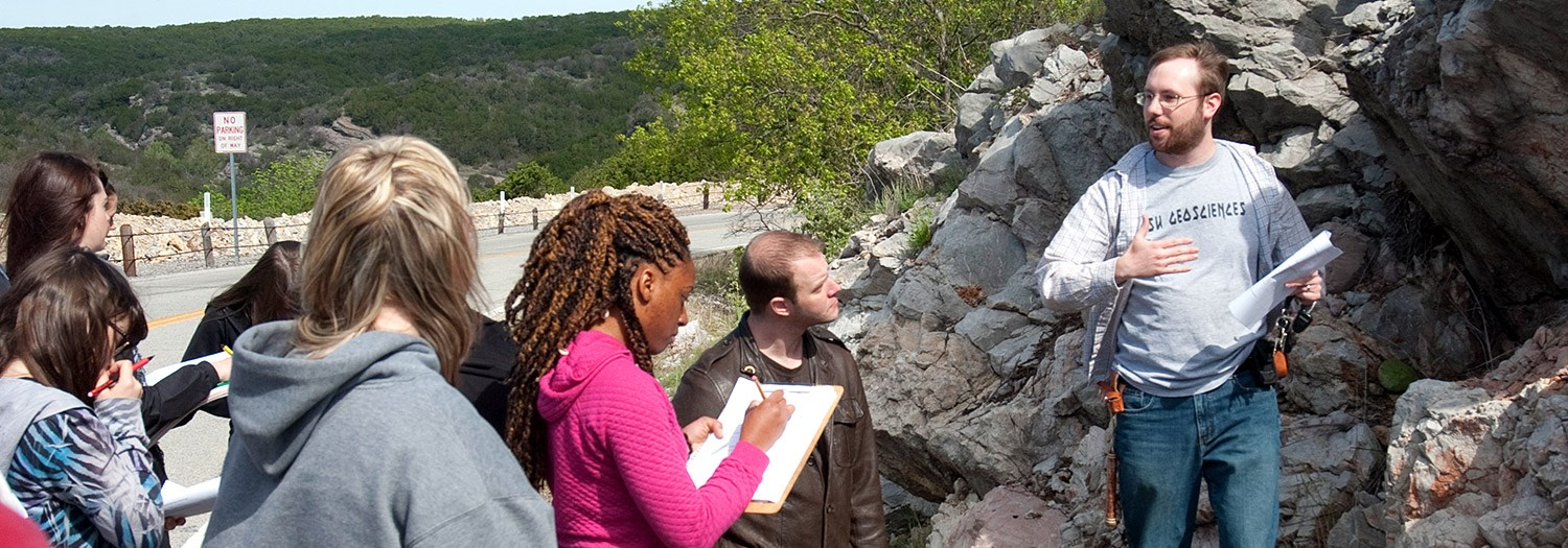 Students with a professor analyzing a rock formation