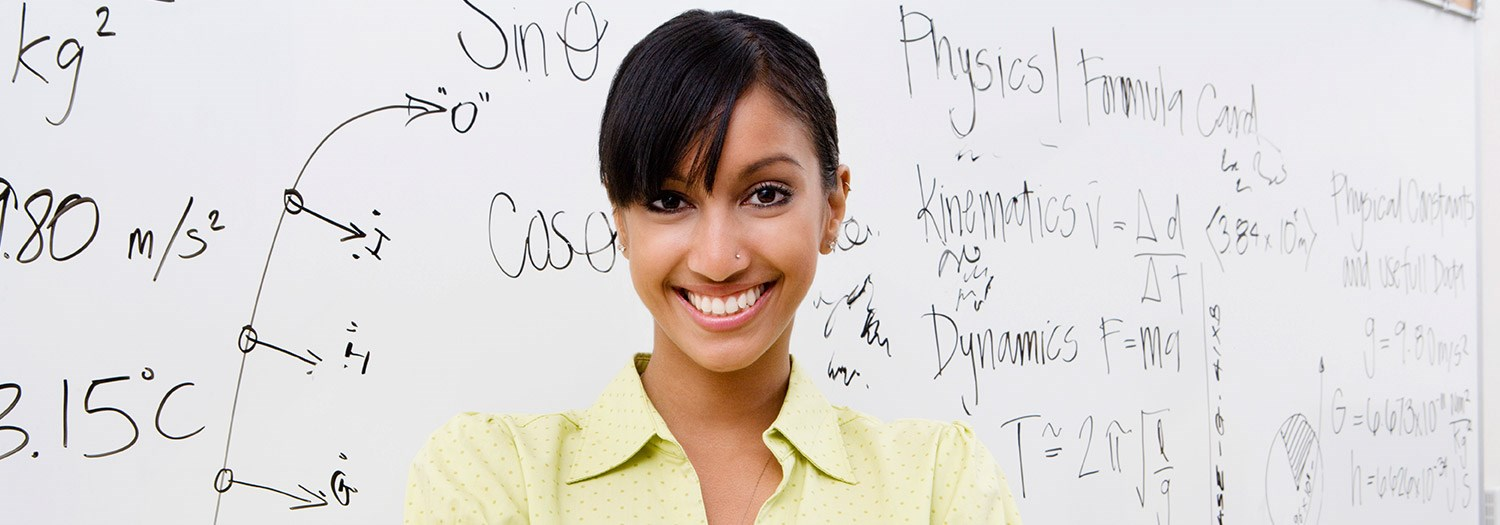 smiling female student standing in front of a white board containing equations