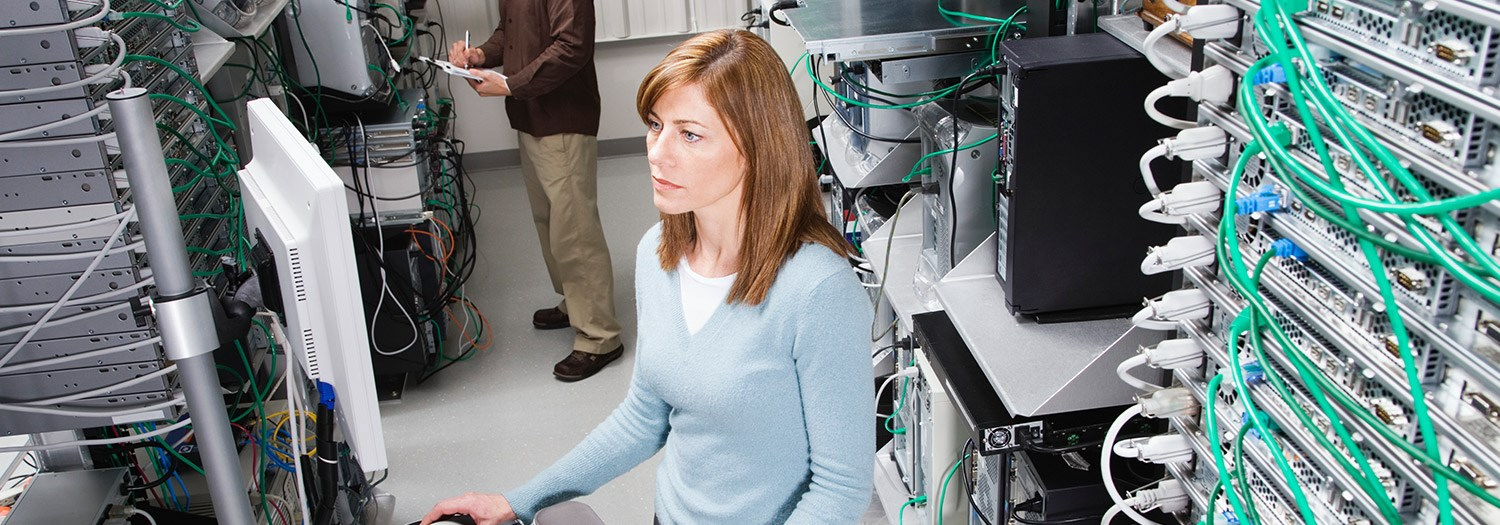 Young lady surrounded by network servers in racks