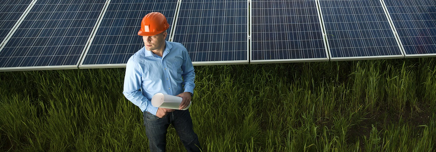 A man in front of a bank of solar panels