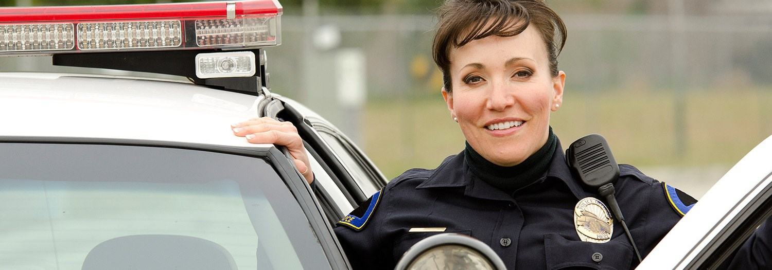 Smiling police officer standing at door of her car