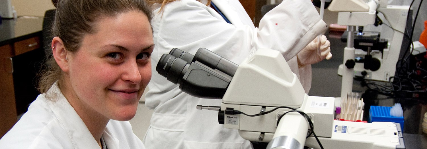 Young lady in front of a microscope
