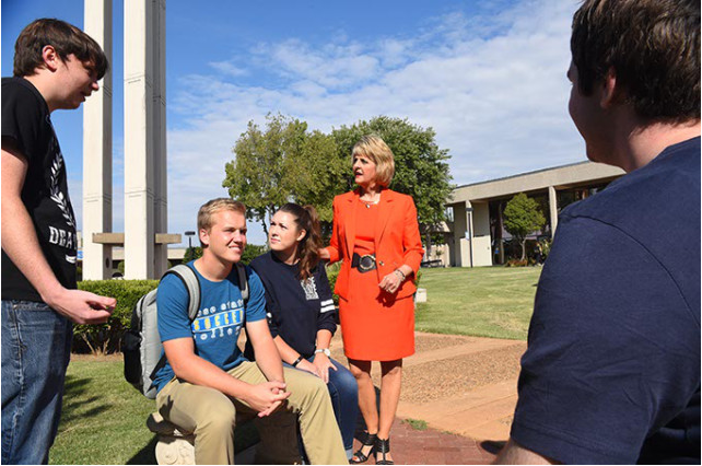 Jeanie Webb, President of Rose State College, chats with a group of students out on the campus. (Mark Hancock)