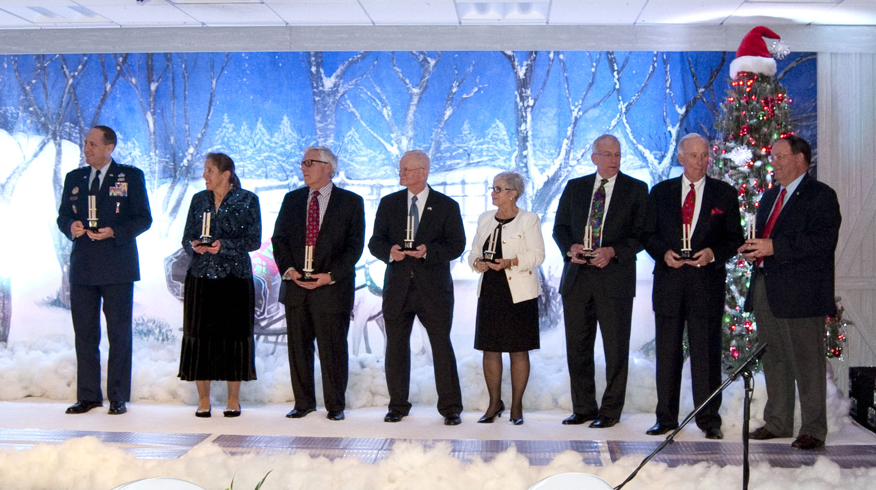 "Eight generals accept awards from President Jeanie Webb at the Regents Christmas Dinner 2015. Pictured from left to right:  Lieutenant General Lee K. Levy II, Linda Litchfield (accepting on behalf of Lieutenant General Bruce Litchfield, Ret.),  Major General Myles Deering, United States Army National Guard Retired and Oklahoma Secretary of Veterans Affairs, Major General William ""Billy"" Bowden, United States Air Force Retired, Major General Rita Aragon, United States Air National Guard Retired and Governor's Liaison for Veterans Affairs, Major General P. David Gillett Jr, United States Air Force Retired, Brigadier General Richard Hefton, United States Air Force Retired, Brigadier General Ben T. Robison, United States Air Force Retired."