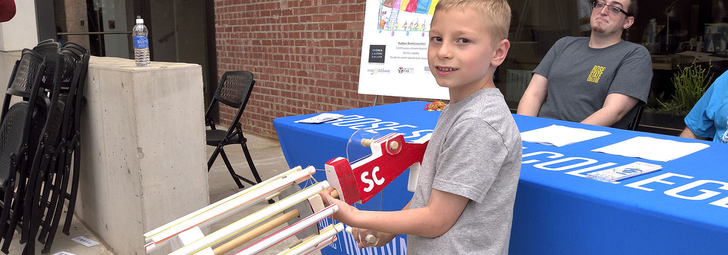 Photo cutline: A second grade student from Soldier Creek Elementary demonstrates the Rubber Band Launcher created as part of the MyMachine initiative.