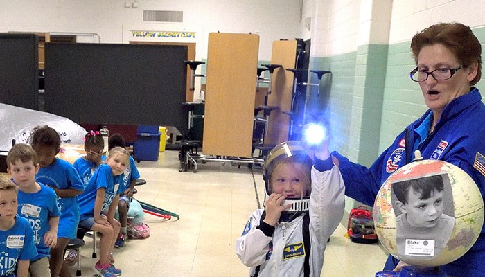 Young Kid's College student dressed in astronaut suit using a flashlight shining on the earth to explain night and day.