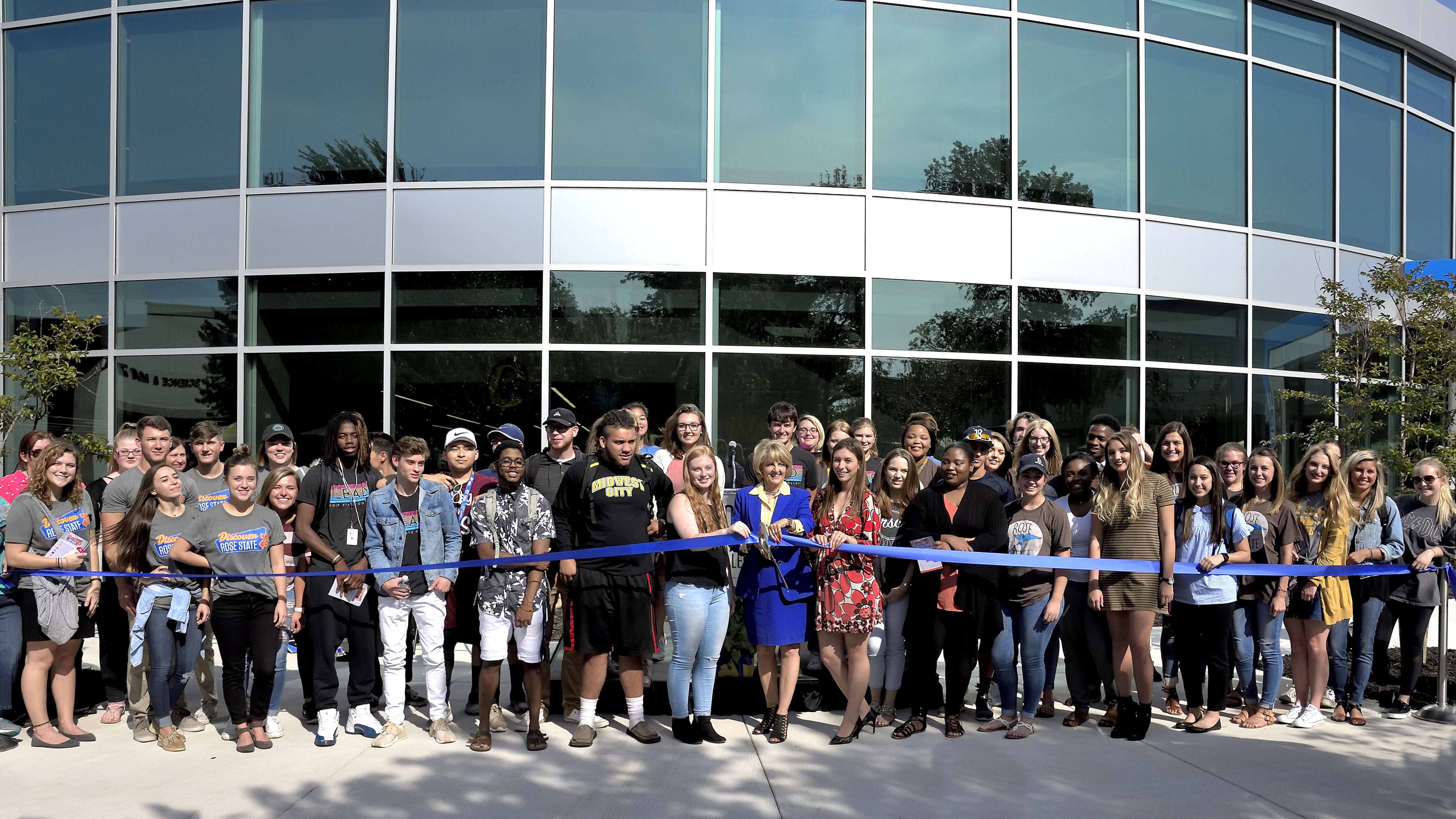 Rose State College President Jeanie Webb cuts the ribbon on the new Learning Resource Center with hundreds of students surrounding her.