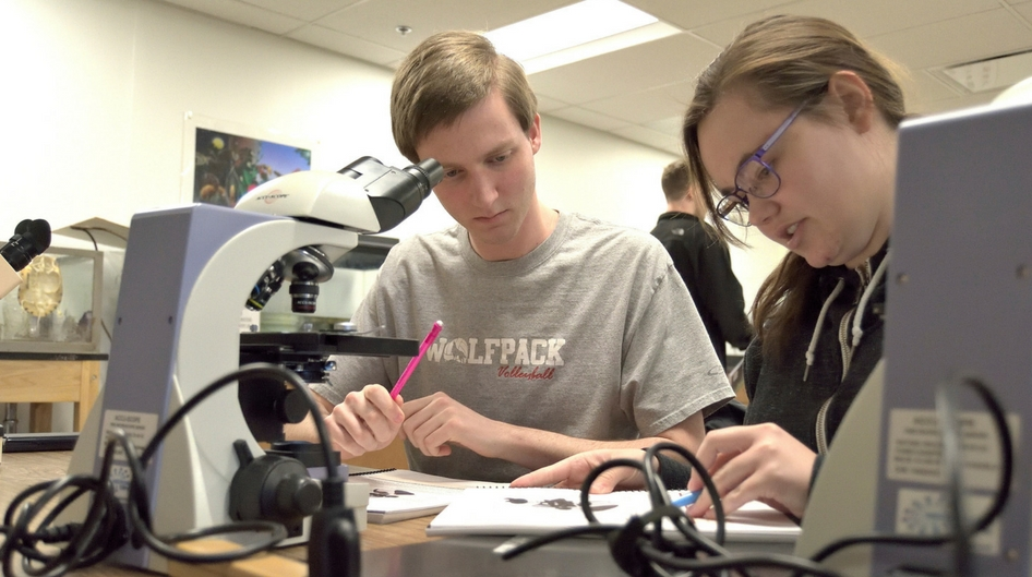 Two students using a microscope in a lab setting