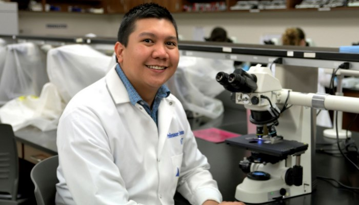 Carlo Ledesma sitting at microscope