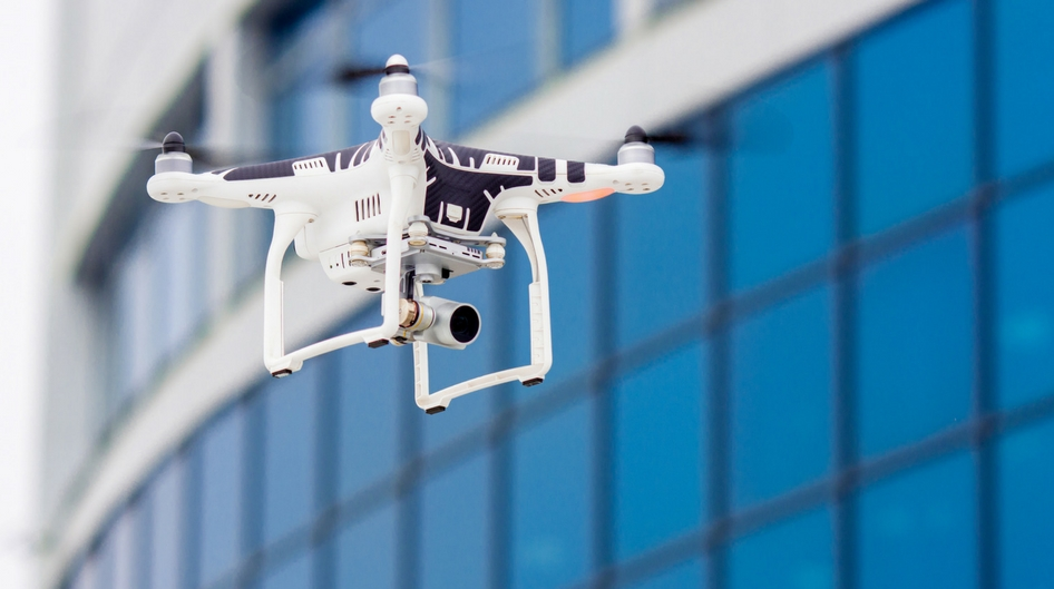 A drone flying in front of a building