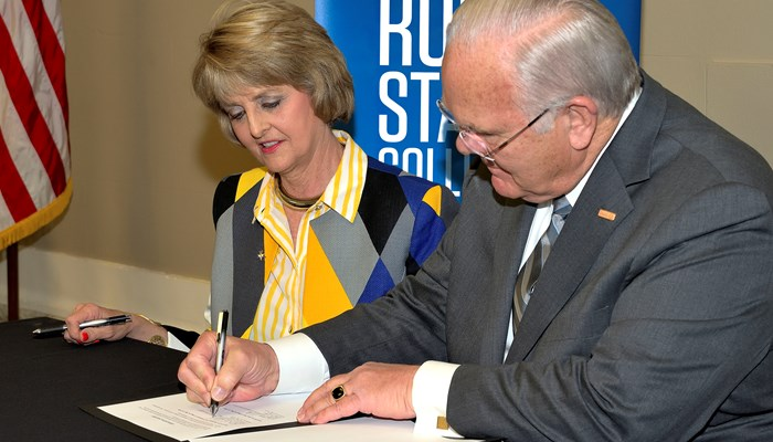 Rose State College President Jeanie Webb and Oklahoma City Community College President Jerry Steward sign the agreement for the colleges to partner on bidding for services.